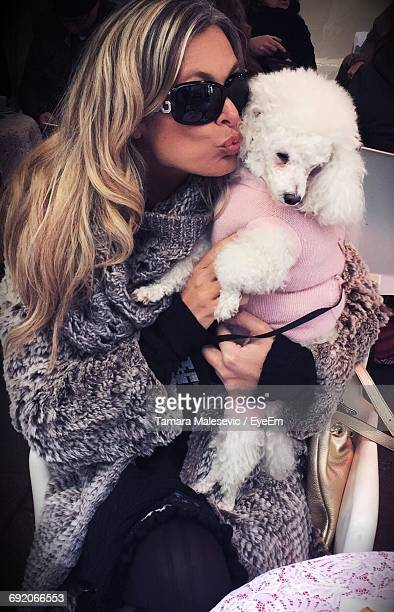 beautiful woman kissing poodle at sidewalk cafe - carnivora stock pictures, royalty-free photos & images