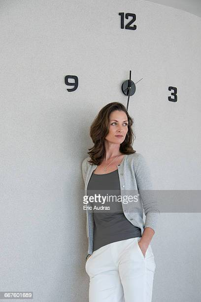 Beautiful woman leaning against a wall and thinking