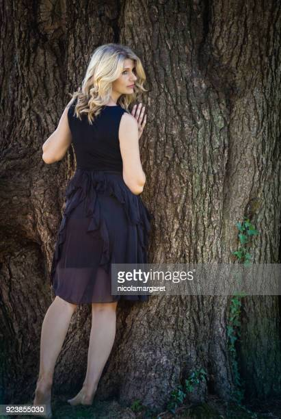 Beautiful woman leaning against tree