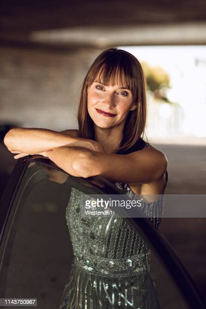 beautiful woman leaning on car - abendkleid stock-fotos und bilder