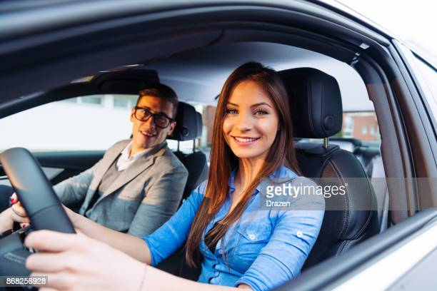 beautiful woman learning to drive a car with professional driving instructor - car pooling stock photos and pictures
