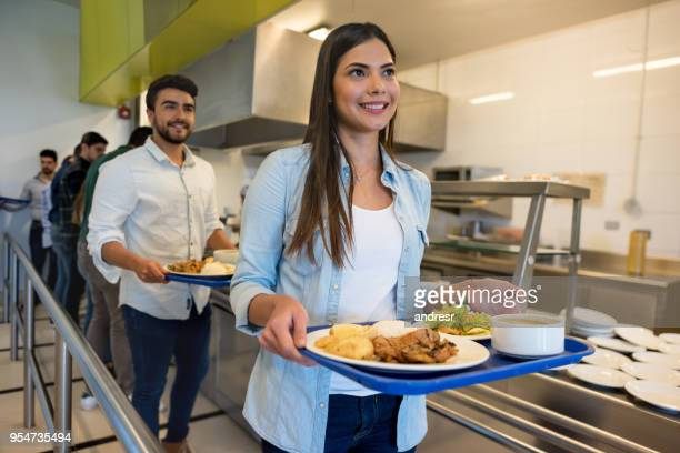 beautiful woman leaving the buffet service with her tray ready to eat lunch - tray stock pictures, royalty-free photos & images