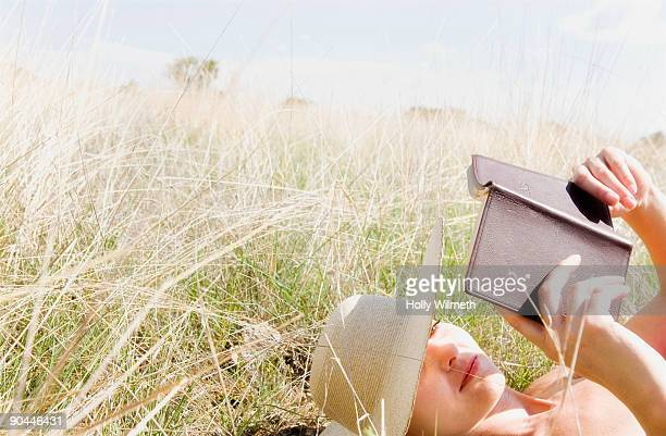 Beautiful woman lies in field and reads.