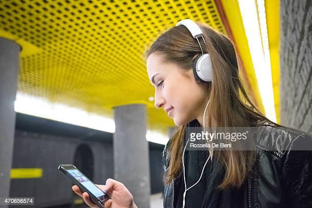 Beautiful Woman Listening Music On Her Smartphone, Subway Station