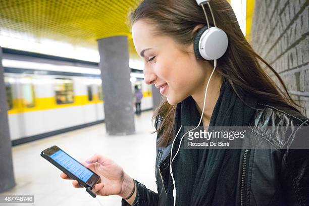 Beautiful Woman Listening Music On Her Smartphone, Subway Train Background
