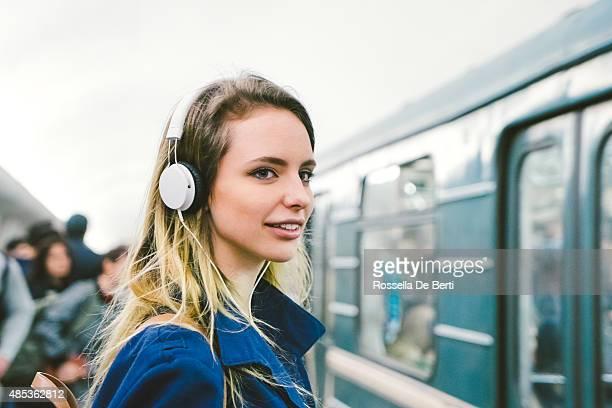 Schöne Frau hören Sie Musik auf Ihrem Smartphone, U-Bahn im Hintergrund