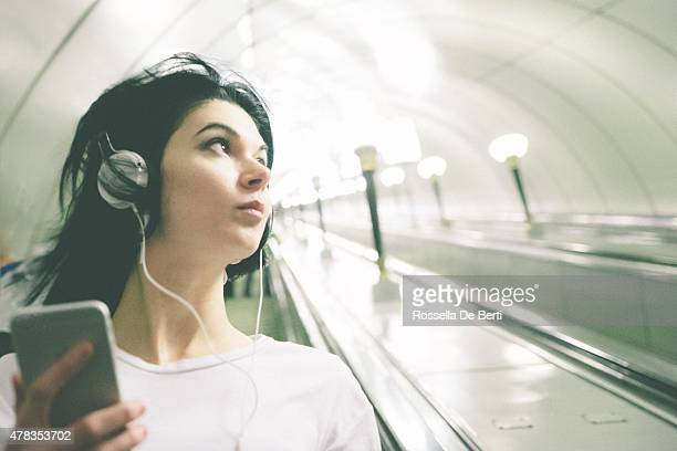 Beautiful Woman Listening Music On Her Smartphone While On Escalator