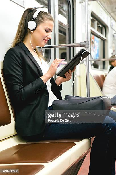 Splendida donna ascoltando musica con il suo Tablet in treno della metropolitana
