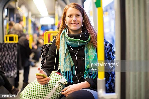 Schöne Frau hören Sie Musik von Ihrem Telefon auf dem