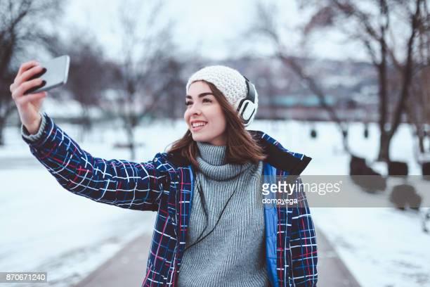 Belle femme écoutant de la musique sur une journée d'hiver
