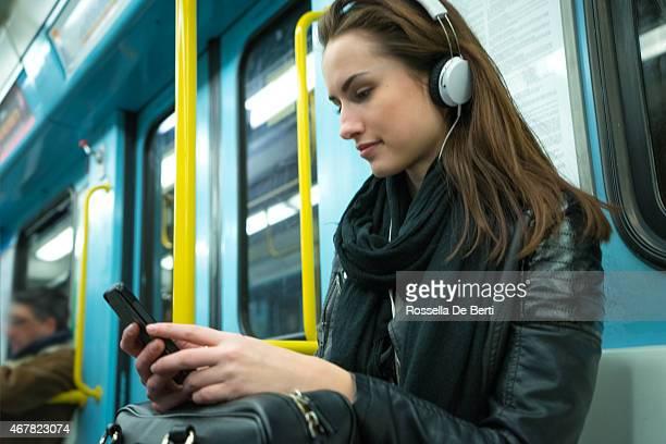 Beautiful Woman Listening To Music On Subway Train