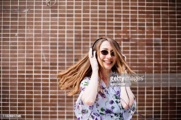 belle femme écoutant la musique - gogo danseuse photos et images de collection