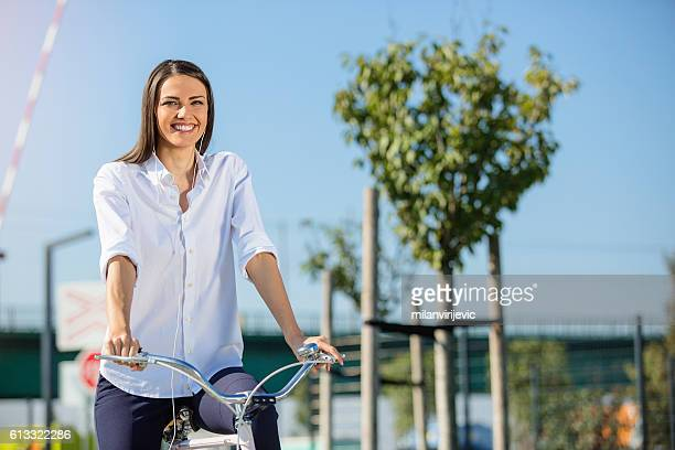 Beautiful woman listening to the music while riding a bike