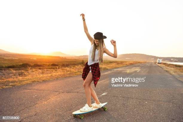 beautiful woman longboarding on country road - longboard skating stock pictures, royalty-free photos & images