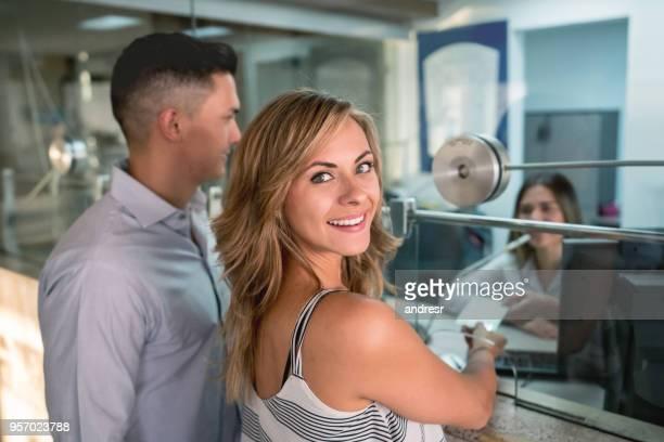 belle femme regardant les commandes de la caméra à côté de son partenaire au box office prêt à regarder un film - hygiaphone photos et images de collection