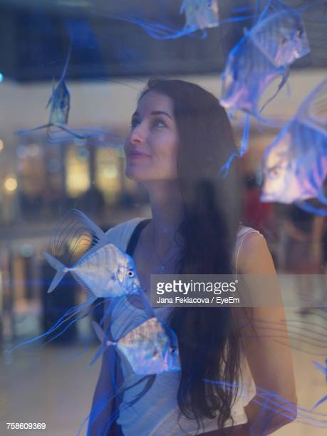 Beautiful Woman Looking At Fishes In Aquarium Seen Through Glass