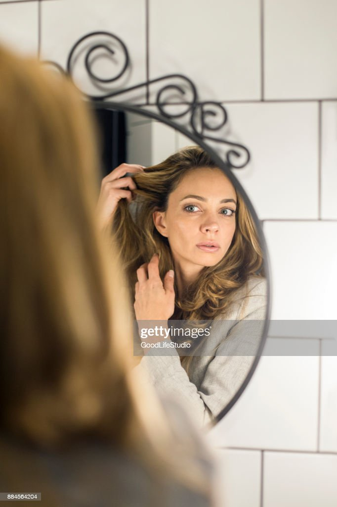 Beautiful woman looking at her hair : Stock Photo
