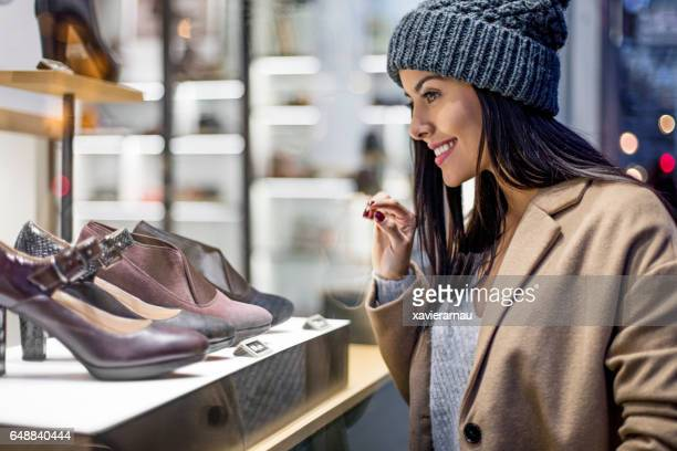 Beautiful woman looking at high heels in store