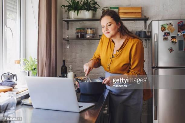 belle femme regardant la recette sur son ordinateur tout en fouettant la crème - une seule femme d'âge moyen photos et images de collection