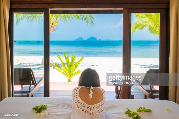 beautiful woman looking away at the beach from a beachfront bungalow, thailand. - looking at view stock pictures, royalty-free photos & images