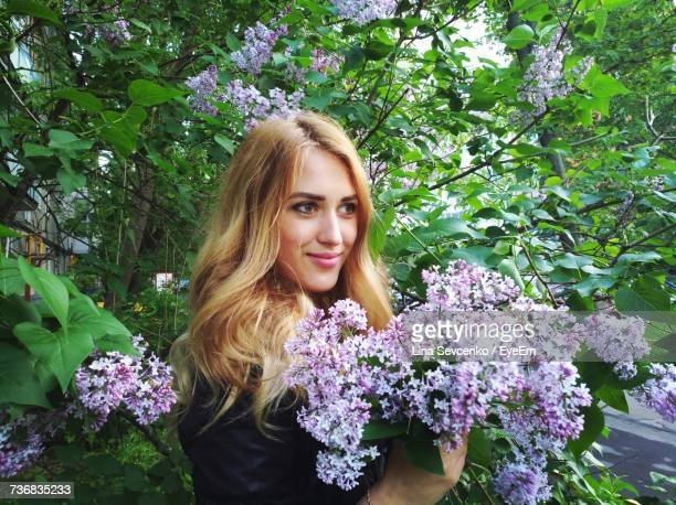 beautiful woman looking away while standing by lilac tree - purple lilac stock pictures, royalty-free photos & images