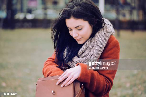 beautiful woman looking for something in her purse - handbag stock pictures, royalty-free photos & images