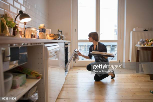 beautiful woman looking in oven while holding baking sheet in kitchen - weiblichkeit stock-fotos und bilder