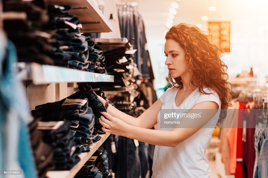 Beautiful woman looking jeans in the boutique. : Stock Photo