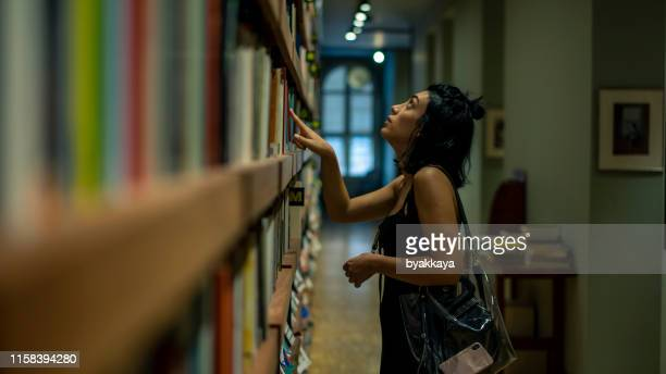 beautiful woman looking out from book in the library - textbook stock pictures, royalty-free photos & images
