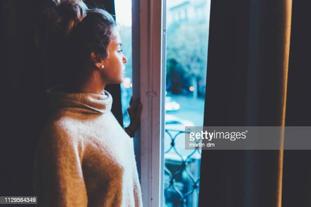 beautiful woman looking out the window - sadgirl stock pictures, royalty-free photos & images