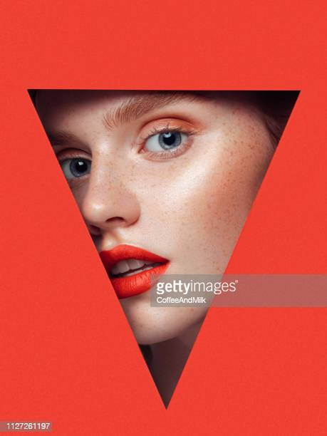 beautiful woman looking through a triangular hole. - hole stock pictures, royalty-free photos & images