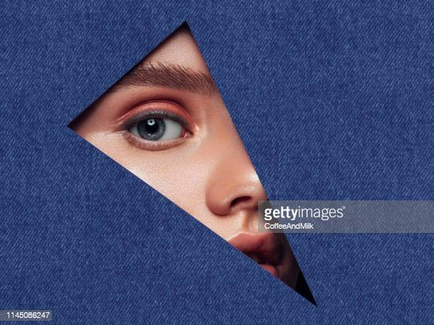 beautiful woman looking through a triangular hole. - women wearing see through clothing stock pictures, royalty-free photos & images