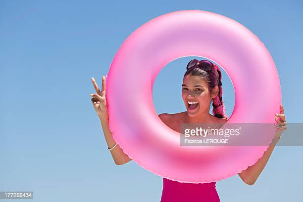Beautiful woman looking through an inflatable ring on the beach