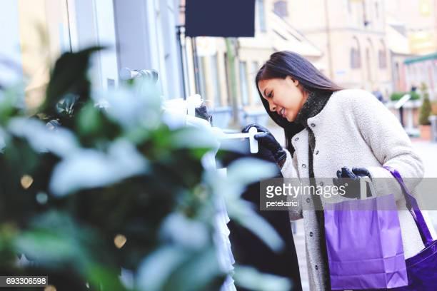 Vacker kvinna tittar genom kläder