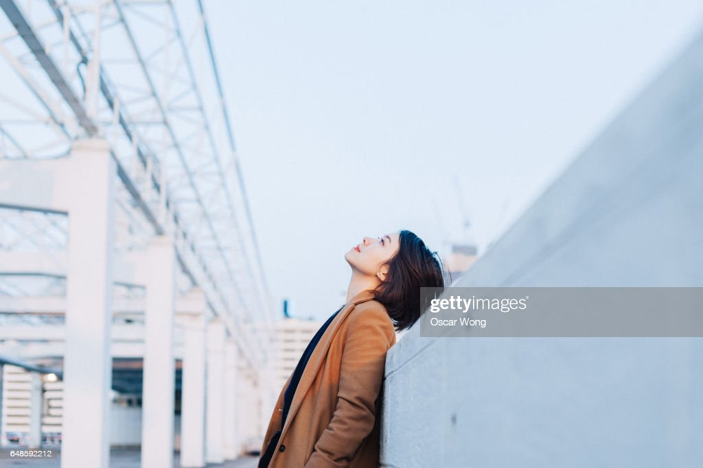 Beautiful woman looking up at outdoor car park : Stock Photo