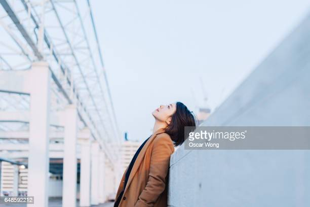 beautiful woman looking up at outdoor car park - looking up stock pictures, royalty-free photos & images