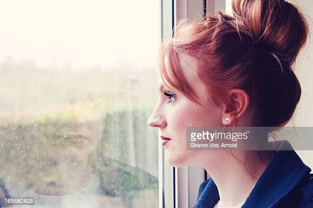 Beautiful woman looking wistfully out of the windo