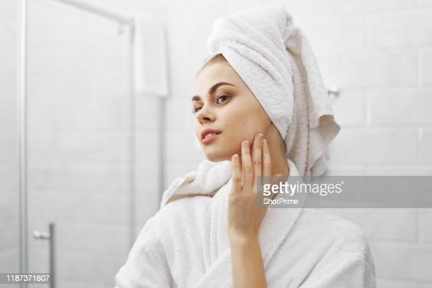 a beautiful woman looks in the mirror in the bathroom, care for the skin - clear sky stock pictures, royalty-free photos & images