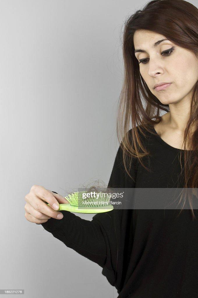 Beautiful woman losing hair on hairbrush : Stock Photo