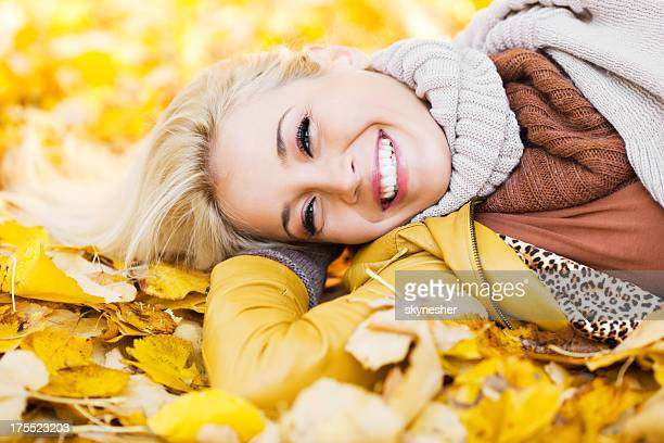 Beautiful woman lying among leaves on sunny autumn day