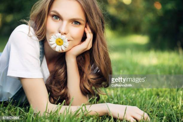 beautiful woman lying down on a grass - chamomile tea stock photos and pictures