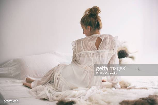 Beautiful woman lying in bed in white dress