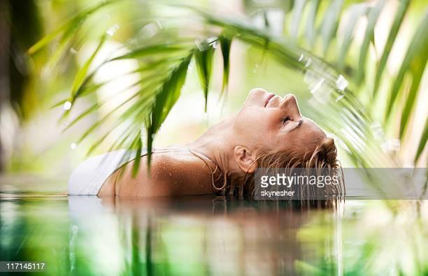 Beautiful woman lying in the tropical pool.