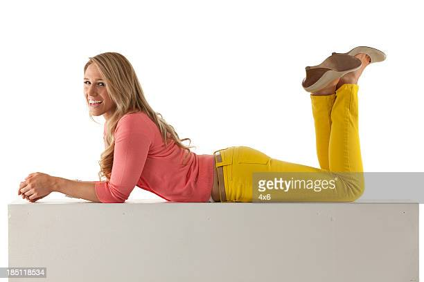 beautiful woman lying on a ledge - lying on front stock pictures, royalty-free photos & images