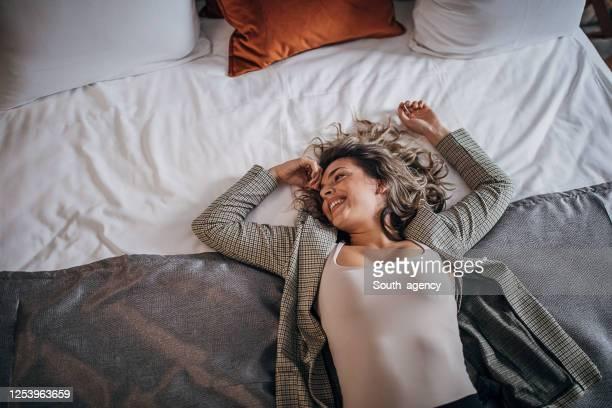 belle femme se trouvant sur le bâti dans la chambre d'hôtel - grand lit photos et images de collection
