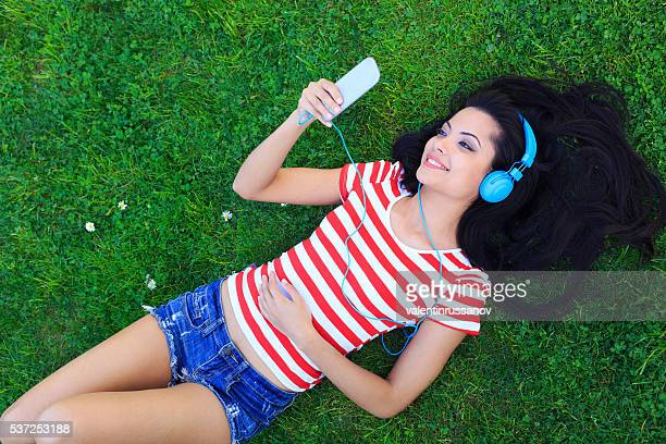 Beautiful woman lying on grass and listening music