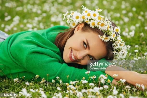 schöne frau auf dem gras liegen - junge frau allein stock-fotos und bilder