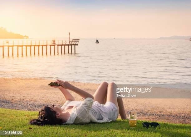 夕日を見てリラックスしたビーチでの幸福と草の上に横たわる美人