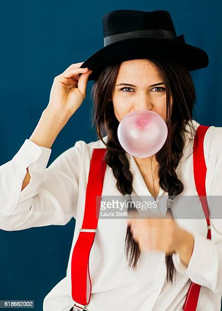 Beautiful woman makes a chewing gum bubble and looks at the camera