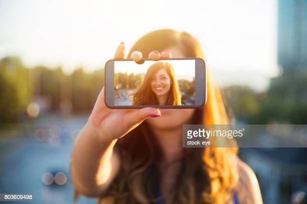 Schöne Frau macht Selbstportrait auf Smartphone-Ansicht des Bildschirms